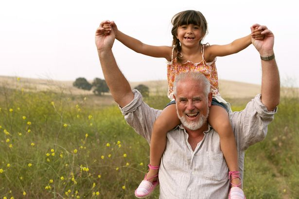 Girl sitting on grandfather's shoulders